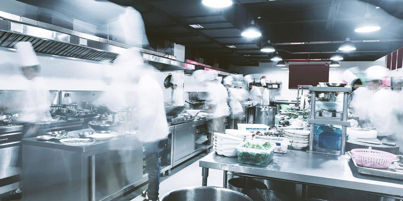 Large commercial kitchen with chefs cooking